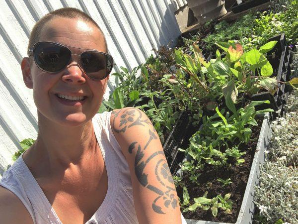 Sara sitter bredvid massor av små plantor.