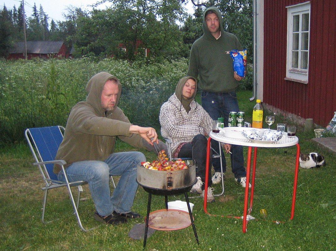 Tre personer grillar i en igenvuxen trädgård framför ett hus.