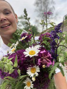 Sara med ett fång trädgårdsblommor