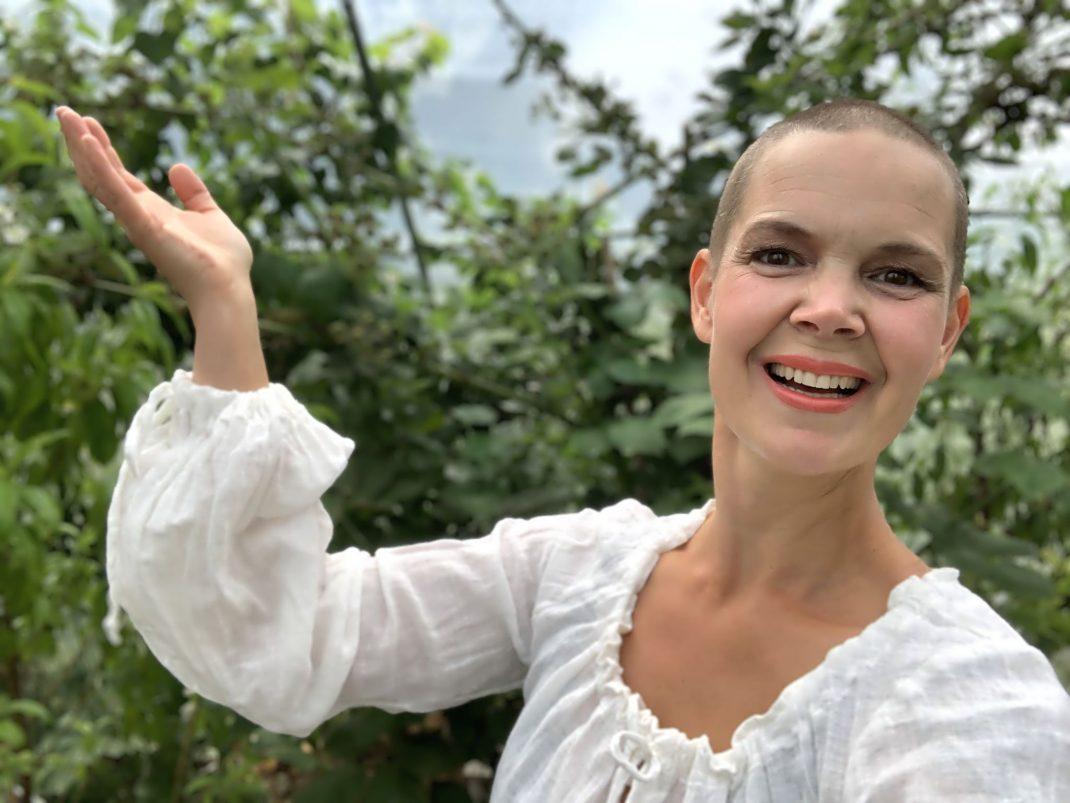 Porträtt av Sara i vit blus mot gröna växter i bakgrunden.