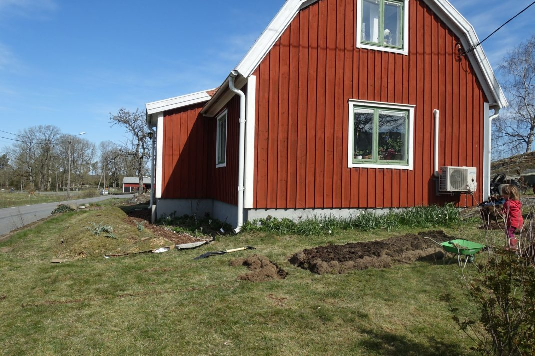 Liten röd stuga med gräsmatta framför