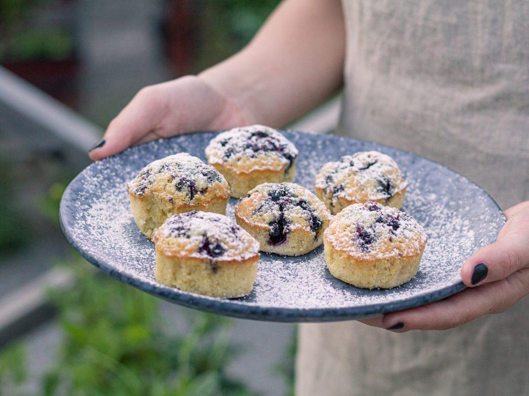 Nybakta blåbärsmuffins pudrade med florsocker serverade på ett blått fat.