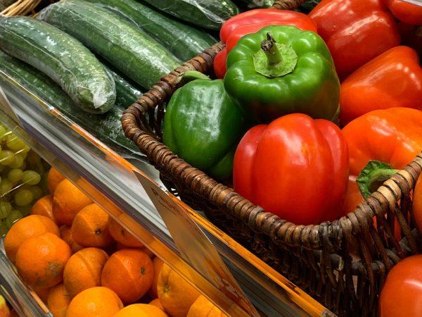 Paprikor och gurkor i en grönsakshylla i butik