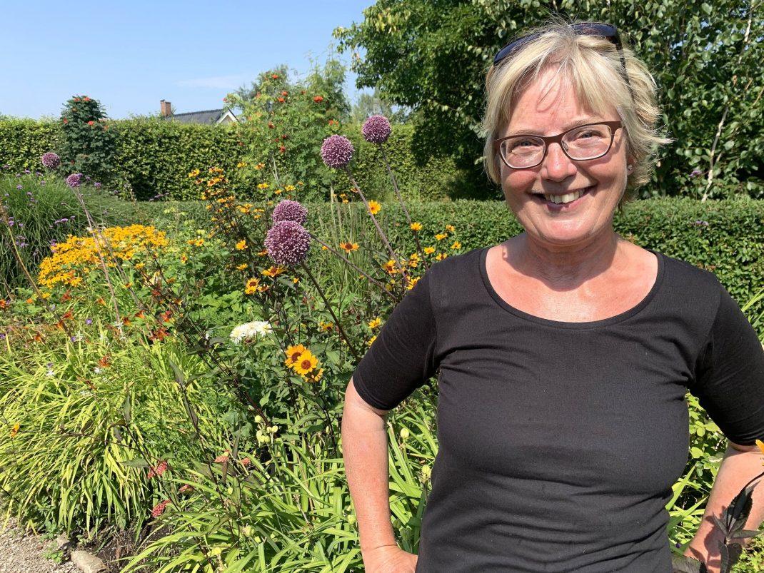 En kvinna i svart t-shirt bredvid höga lökväxter.