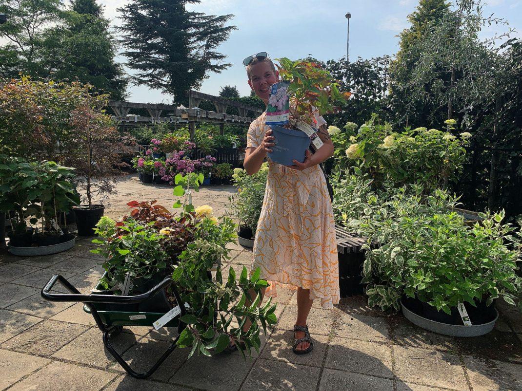 Sara i en plantbutik med en planta i handen.