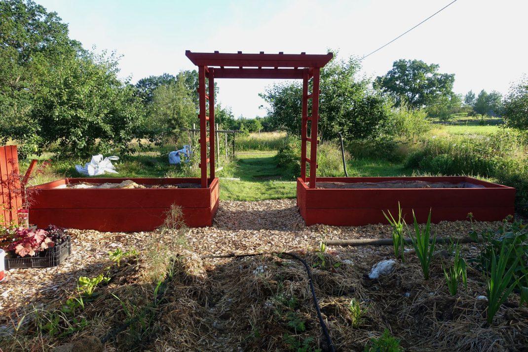 En rödmålad portal mellan två stora odlingslådor.