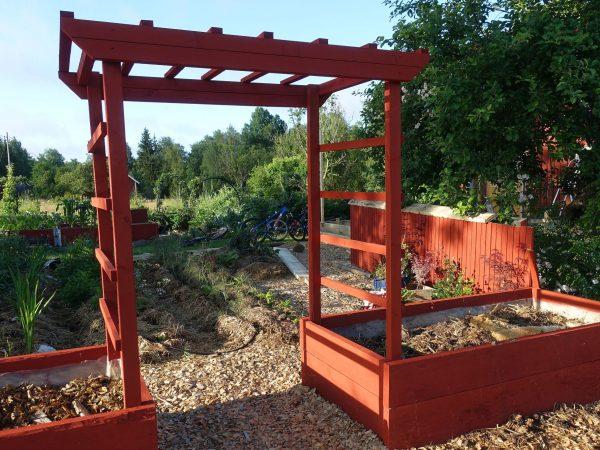 Rödmålad portal av trä i trädgården.