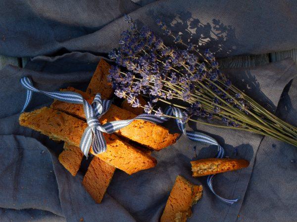 En litet paket av krispiga biscottis med en rosett och en lavendelbukett bredvid.