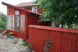 Rödmålat växthus och staket.