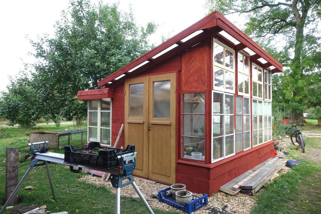 Rött växthus med gula dörrar och en sågbock framför.