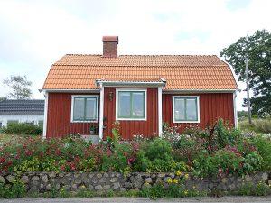 En stenmur och en blomsterrabatt av rosenskäror framför ett rött litet hus.