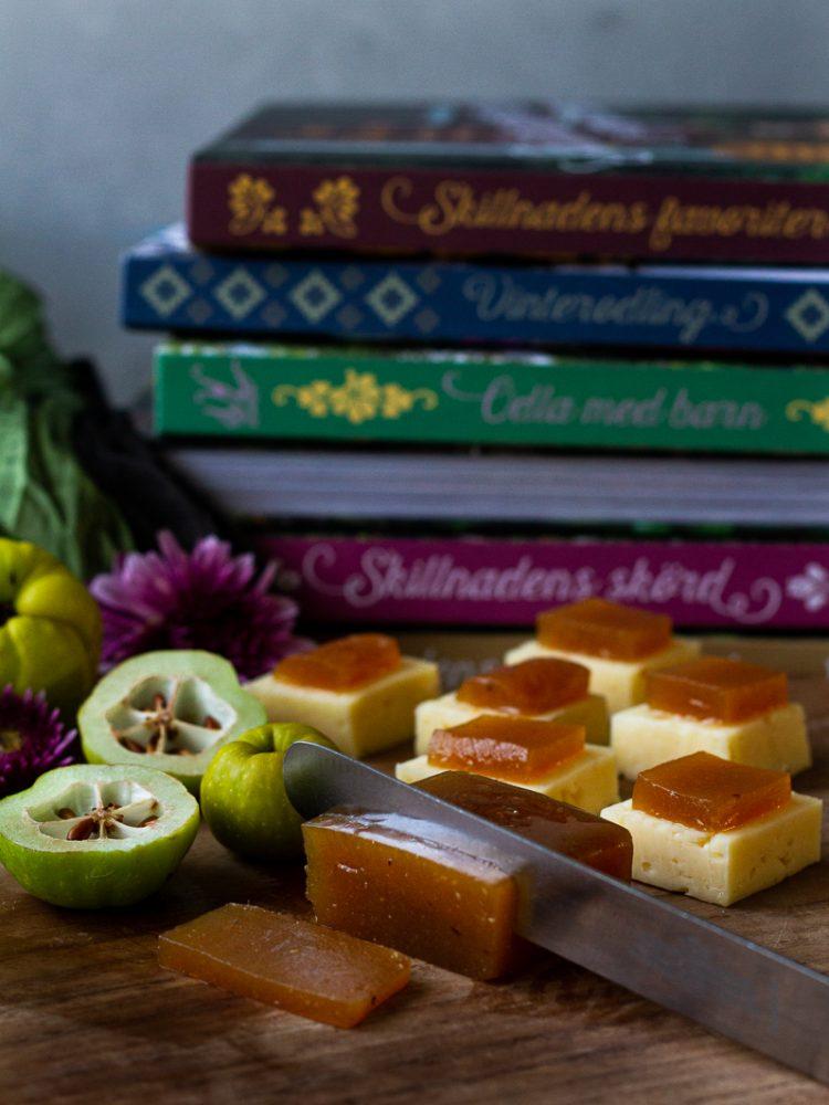 Kvittengelé serverad på en ostbricka och några färska kvittenfrukter.