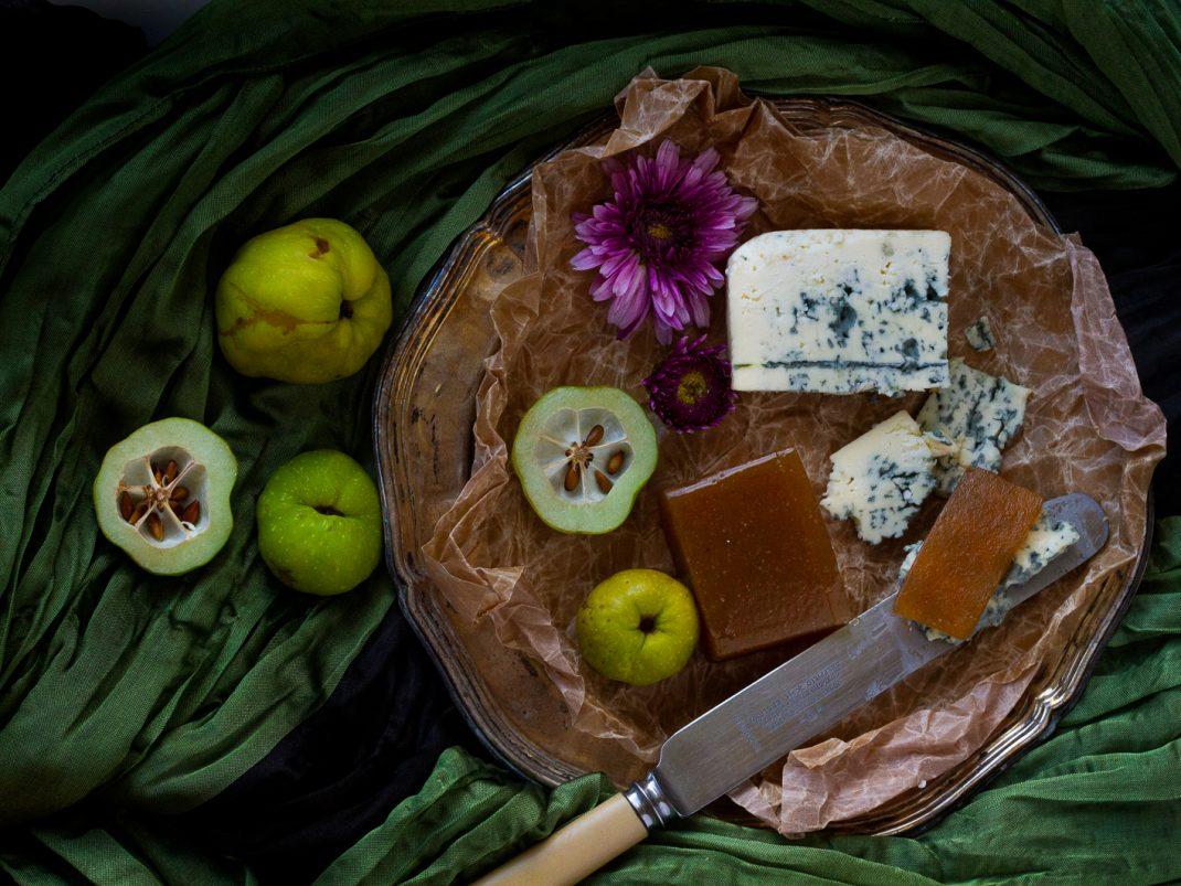 En ostbricka med gele av rosenkvitten och blåmögelost samt några färska kvittenfrukter.
