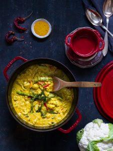 En gyllene currygryta med blomkål och amdra färska grönsaker från trädgårdslandet.