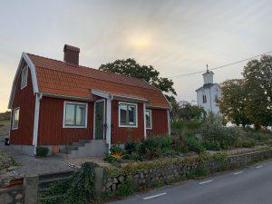 Ett litet rött hus på ett berg.