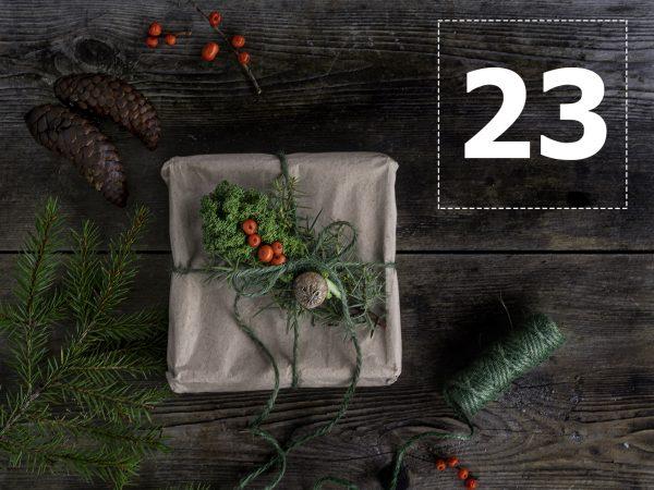 En julklapp i brunt papper och grönt snöre med grane, kottar, grönkål och bär.