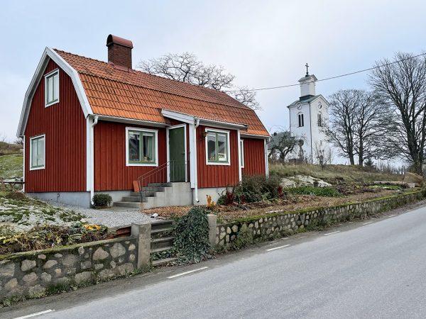 Ett rött litet hus med en köksträdgård i vintervila.