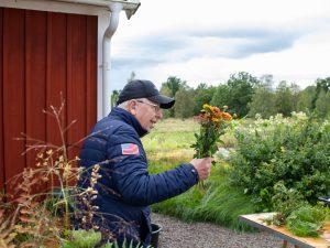 En äldre man med keps och en bukett blommor i handen.