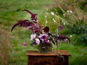 Ett vackert arrangemang av blommor i vinrött och lila.