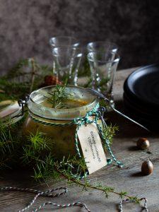 En glasburk med hemmagjord rosmaringgravad strömming. Ett juligt tema med granbarr, kottar, julsnöre, nötter och snapsglas. står