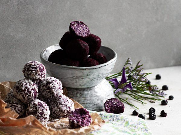 Blåbärsbollar med kokos och blåbärspulver uppdukade i skålar och papper.