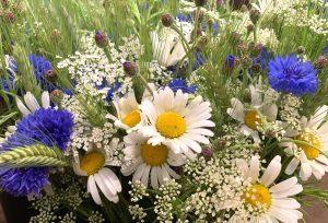 Närbild på blombukett i blå, vita och gula nyanser.