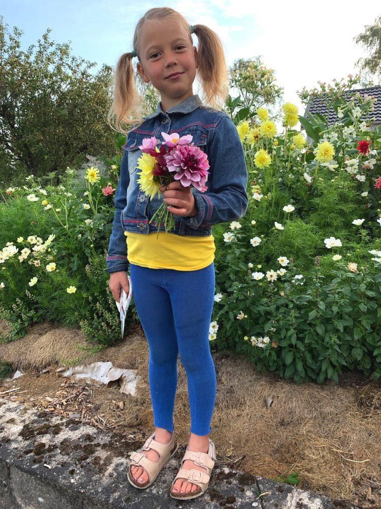 En tjej i blåa kläder och pippitofsar med en blombukett i handen.