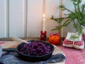 Rödkål i en liten gjutjärnsgryta i en julig inramning med gran, apelsin och juleljus.