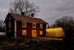 Ett rött hus och ett växthus framför med ljusslingor.