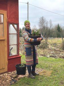 Sara står i randig kofta med en stor kruka i famnen, utanför ett växthus.