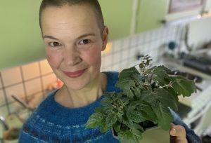 Sara står i ett kök och håller en liten tomatplanta i handen.