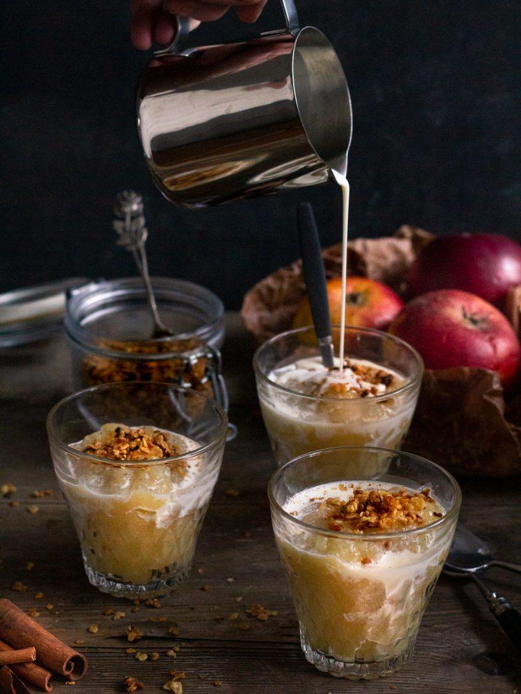 Serveringsglas med fruktkräm och havrecrunch och gräddmjölk, i bakgrunden röda äpplen i brunt papper.