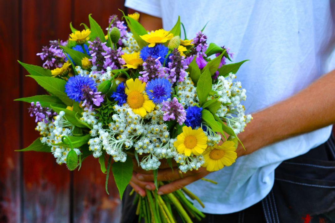 En man i arbetsbyxor håller en färgstark bukett i blått, gult, vitt och lila.