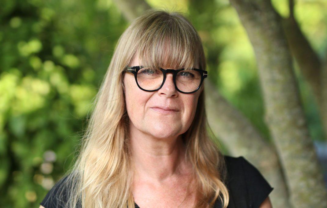 Porträtt av kvinna med långt ljus hår och glasögon.