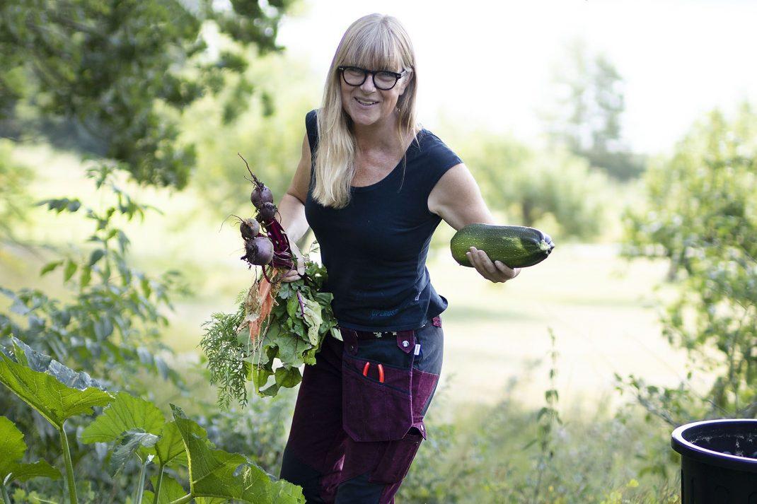 En kvinna med grönsaker i händerna och arbetsbyxor på.