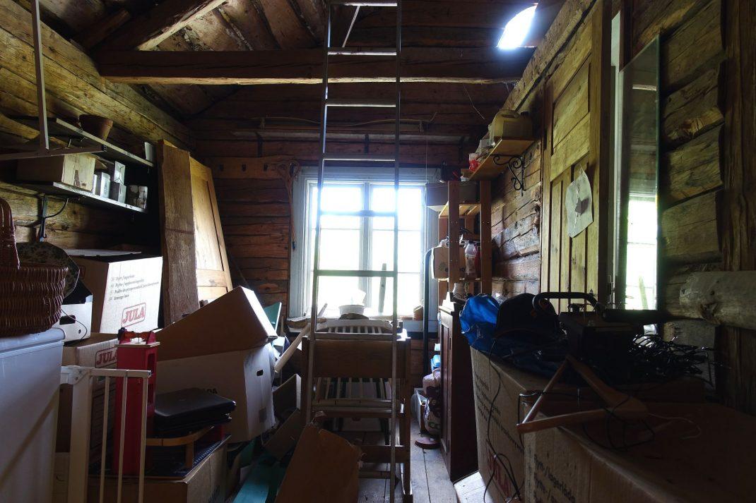 Ett litet rum, öppet till nock i tak, helt fyllt av kartonger och prylar.
