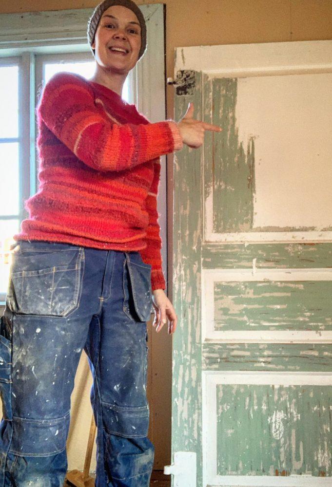 Sara står i arbetskläder bredvid en dörr som skrapas.