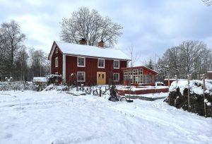 rött hus med massor av snö runtomkring.