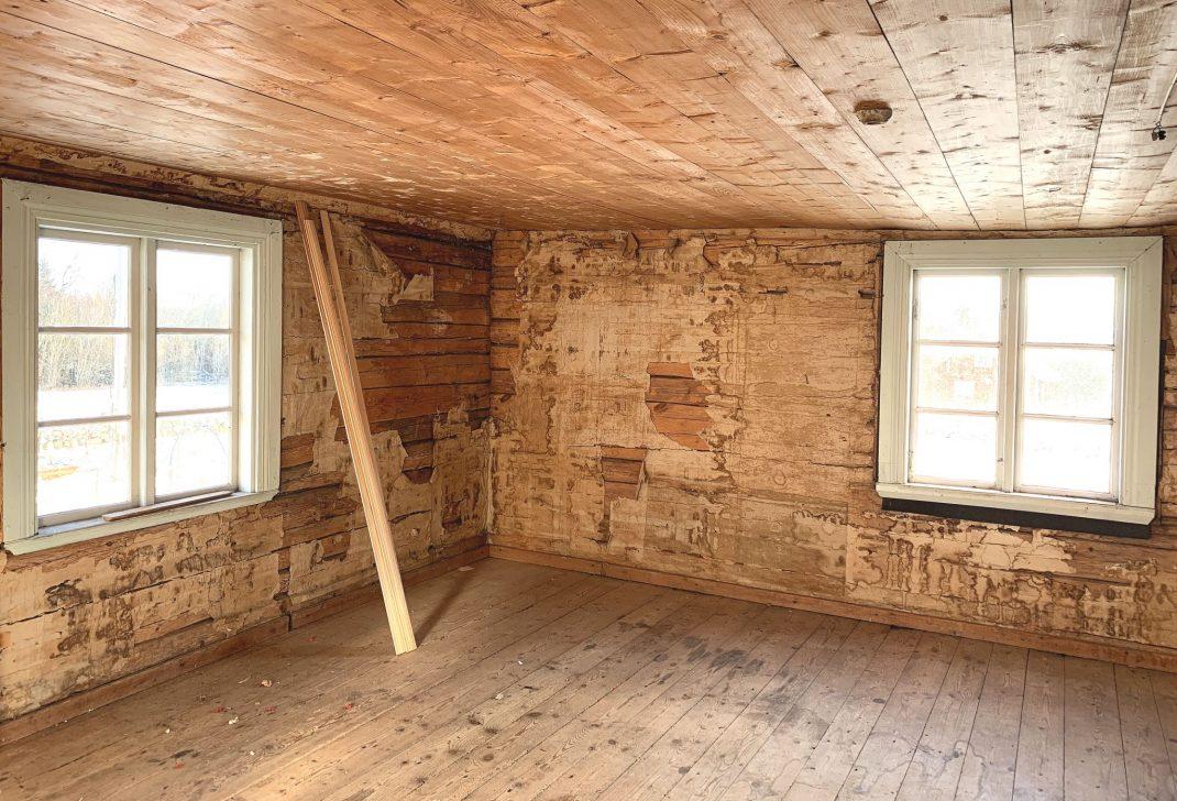 Ett helt tomt gammalt rum i ett timmerhus.