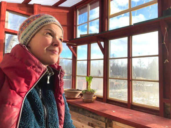 Sara Bäckmo i ett soldränkt växthus snickrat av gamla fönster.