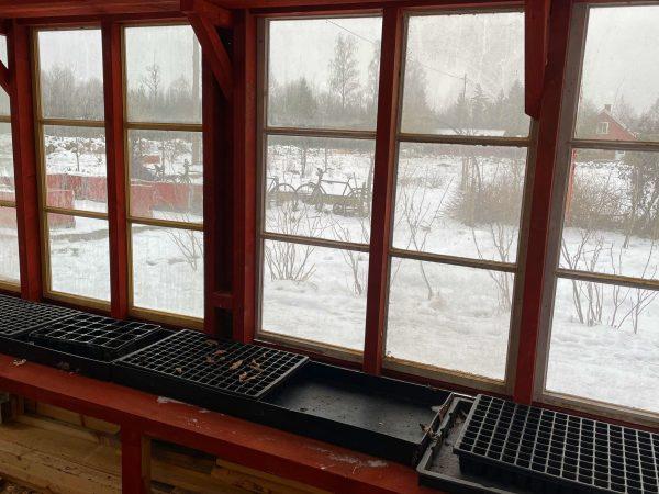 Ett tomt växthus med brätten och brickor på en bänk.