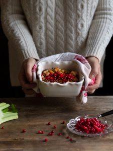 Ett par händer håller fram en läcker form med kålpudding toppad med röda lingon.