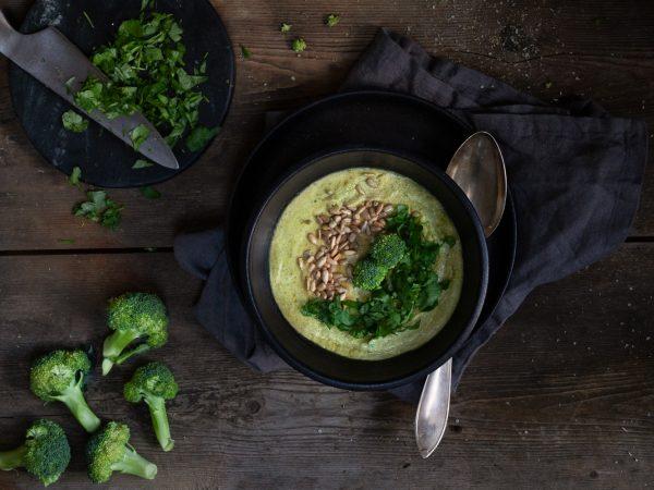 Broccolisoppa i en svart soppskål. Vid sidan syns hackad persilja och broccolibuketter.