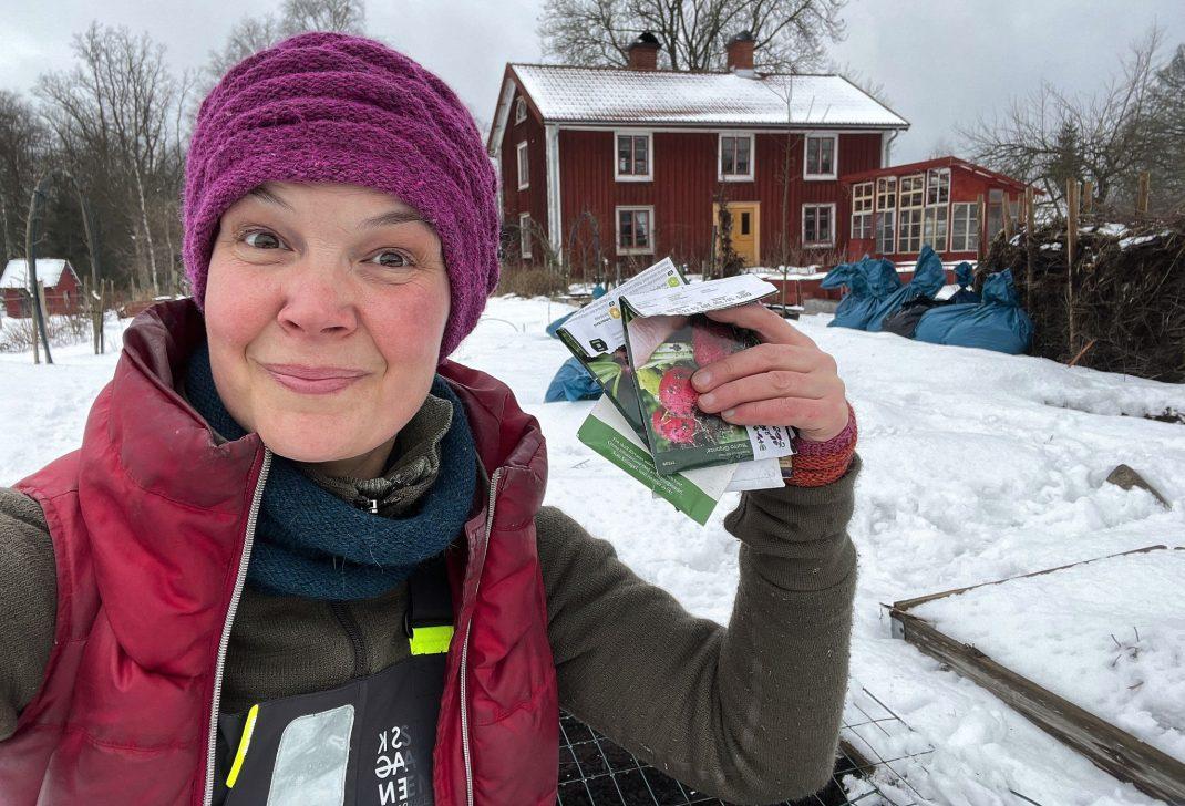 Sara i snön med fröpåsar i handen och ett rött hus i bagrunden.