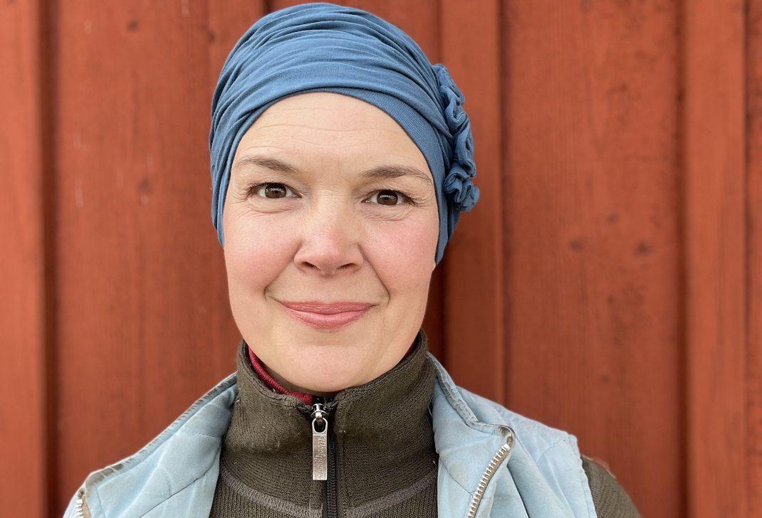 Porträtt på Sara i blå mössa mot röd vägg.