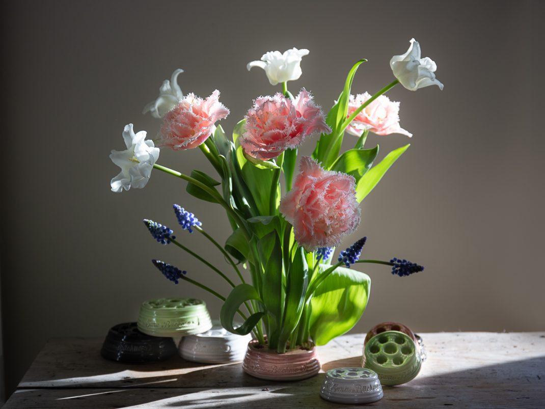 En vacker bukett med tulpaner och blå pärlhyacinterstår fint i en blomhållare i keramik..