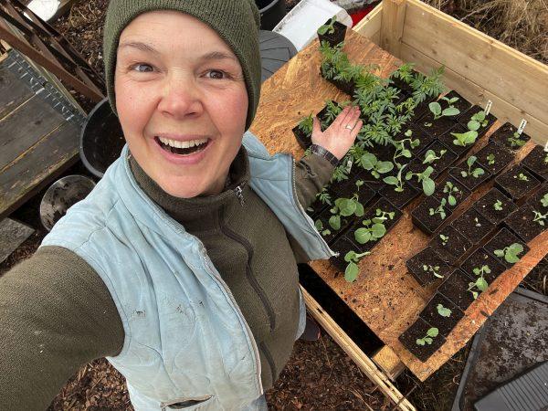 Sara bredvid ett bord av plantor.