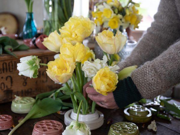 Ett gult och vitt tulpanarrangemang i blomhållare.