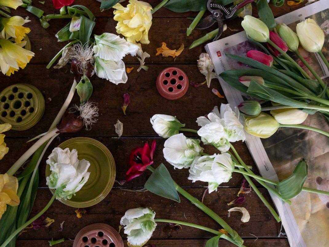 Ett bord med sett ovanifrån med massor av tulpaner och blomhållare.
