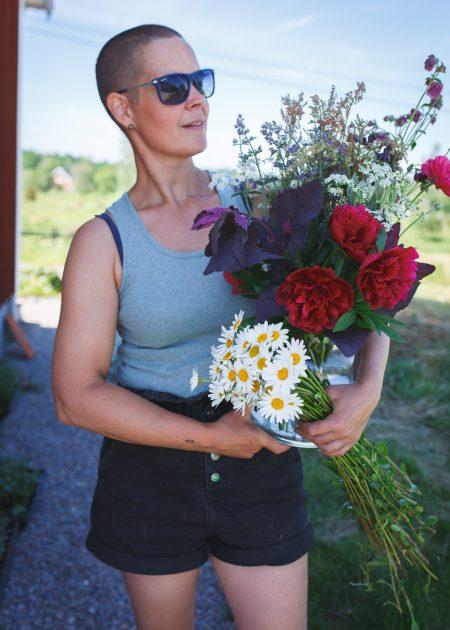 Sara med ett fång blommor från trädgården